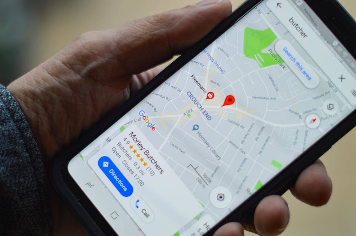 man holds phone with google maps open