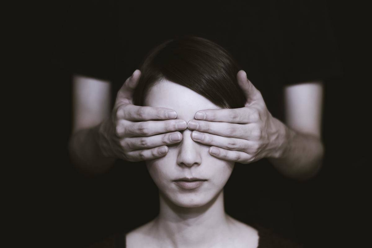 hands cover woman's eyes