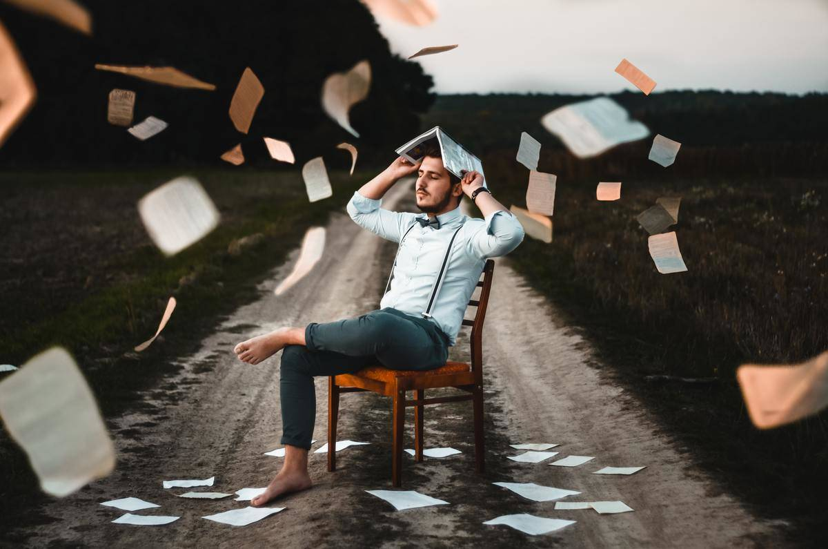 books raining over man sitting in the middle of paved road