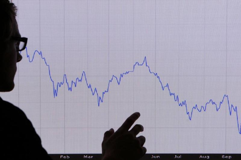 a man looks at a graph representing the 12 month decline of the FTSE 100 share index