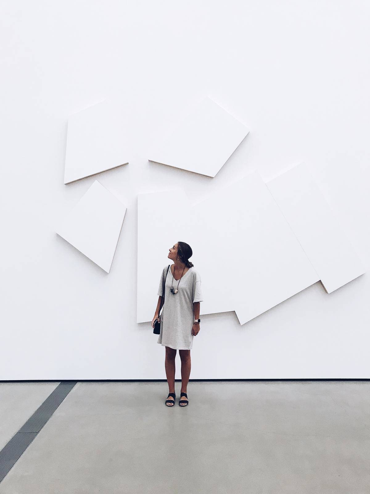 person standing in front of some art at a museum