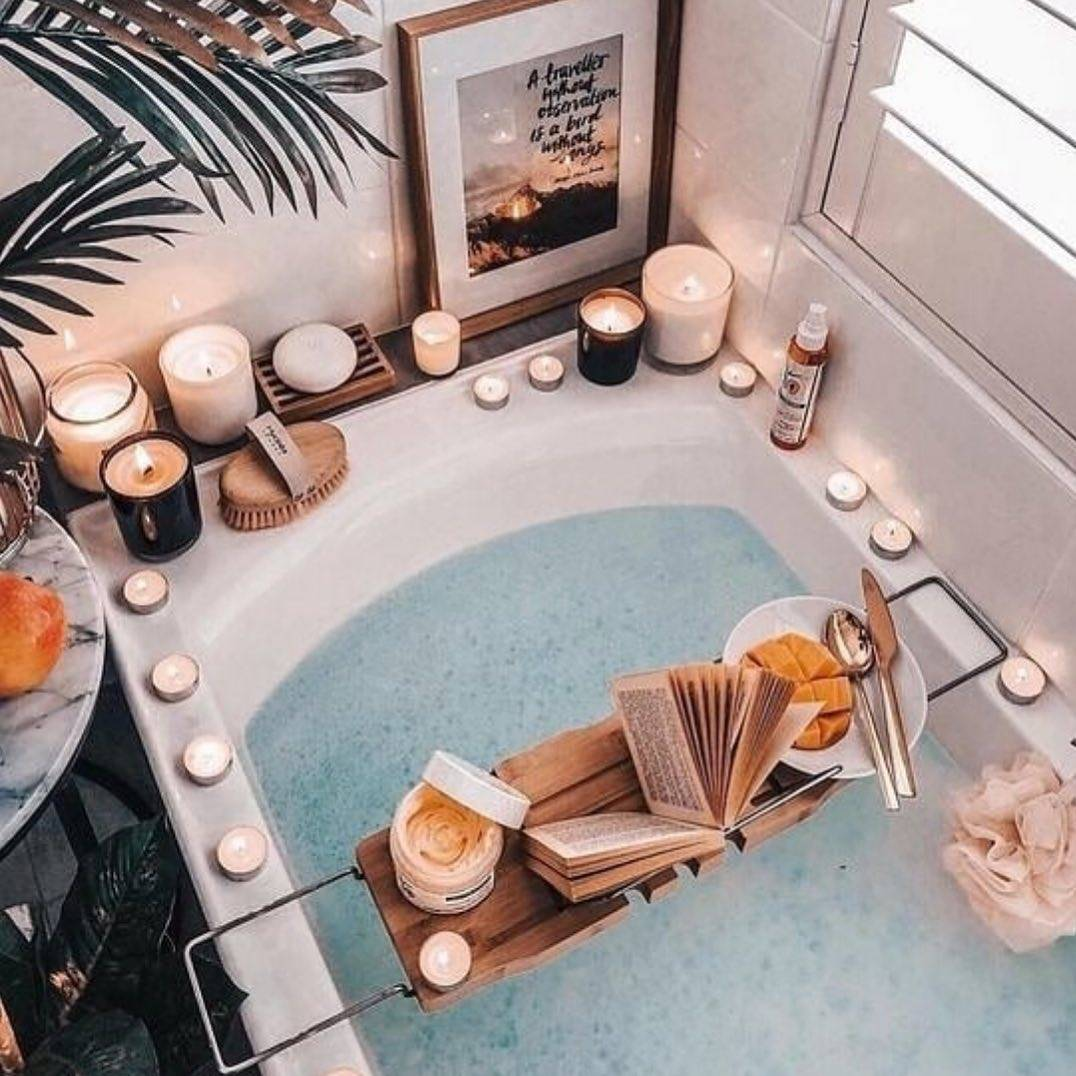 a very inviting bath with lots of candles and a stand that has a book and some fruit on it
