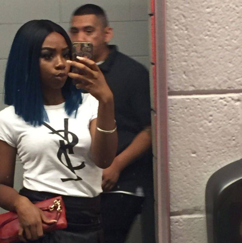 woman taking a selfie in a bathroom not realizing that she was in the men's bathroom