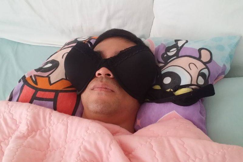 guy wearing a bra covering his eyes