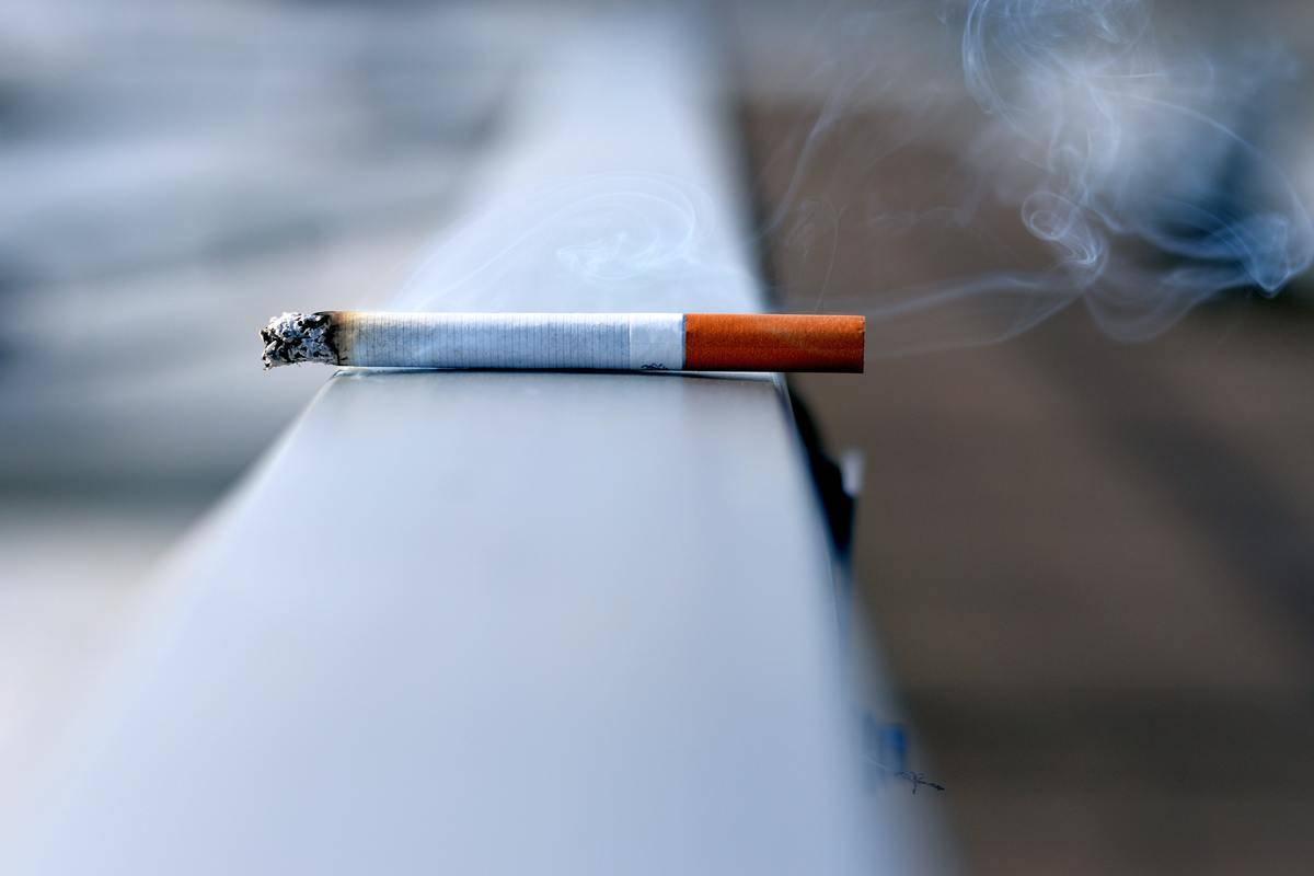 burning cigarette resting on ledge