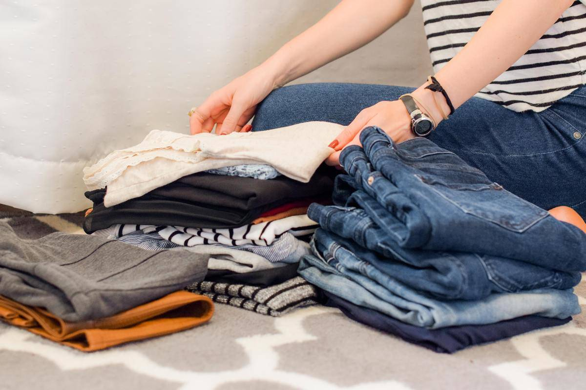 someone going through folded clothes