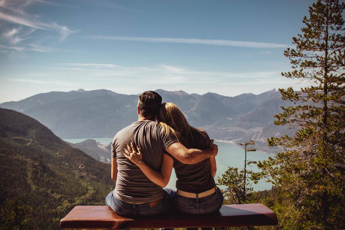 couple sits on bench and takes in the view