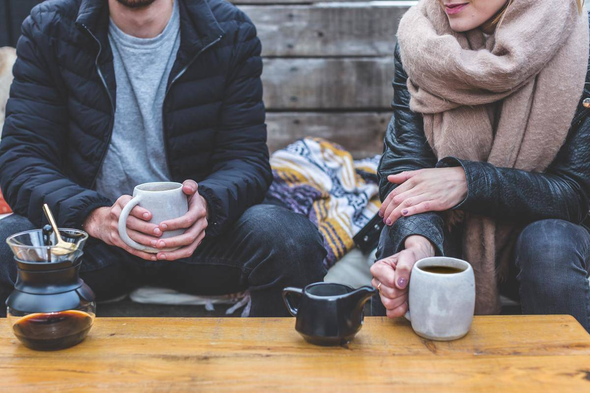 couple seated outside dressed for winter with coffee cups