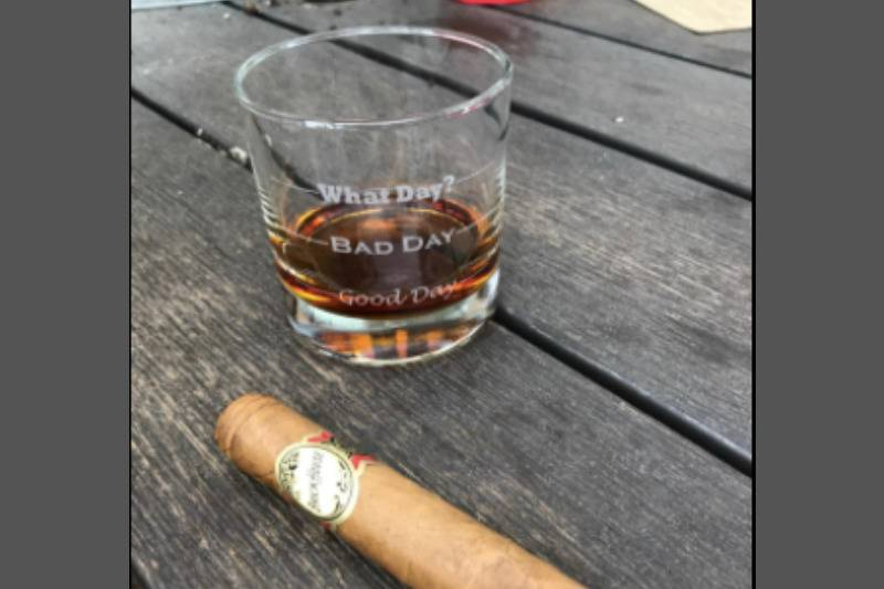 cup with whiskey and cigar on grey wooden table