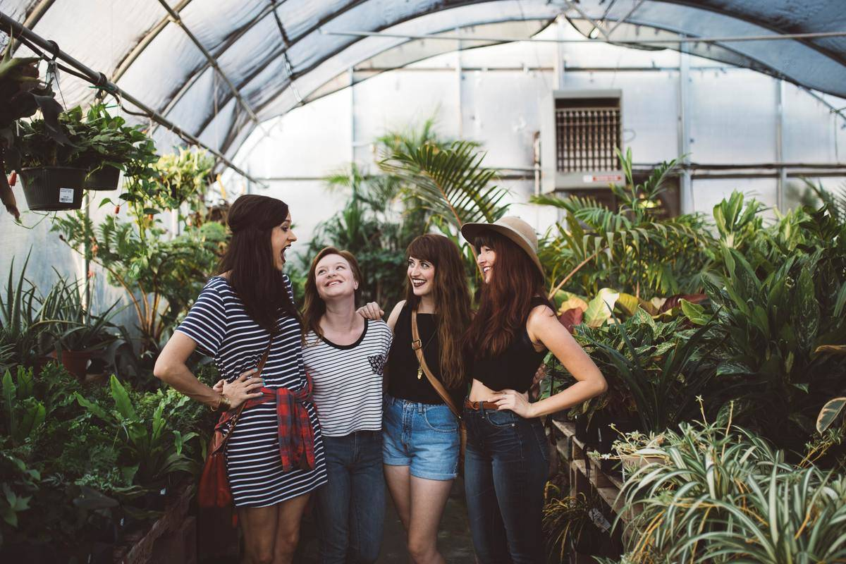 three women in greenhouse smiling looking up at taller friend speaking