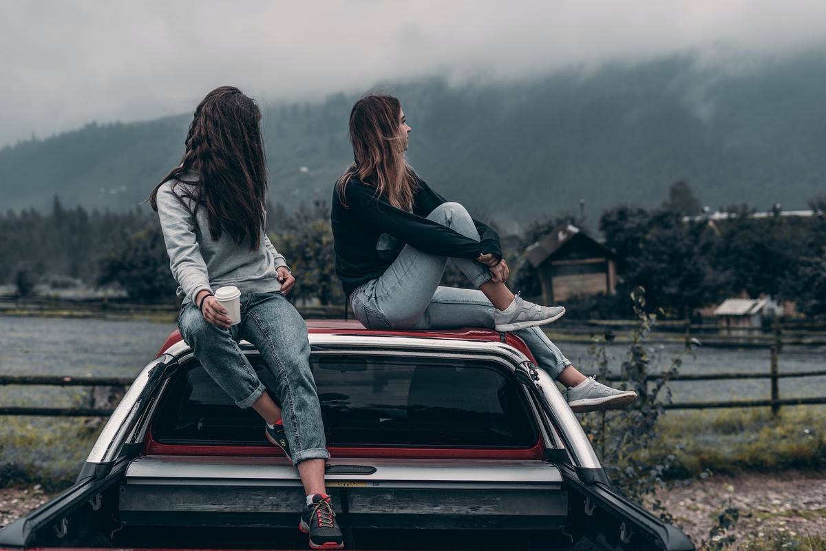 two friends seated on car roof in fog looking away