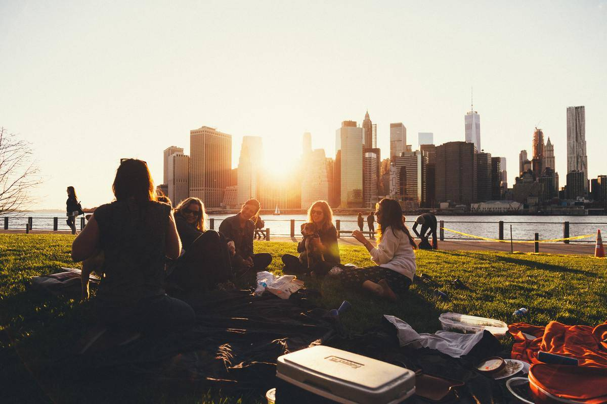 group of friends sitting at parc city skyline in background