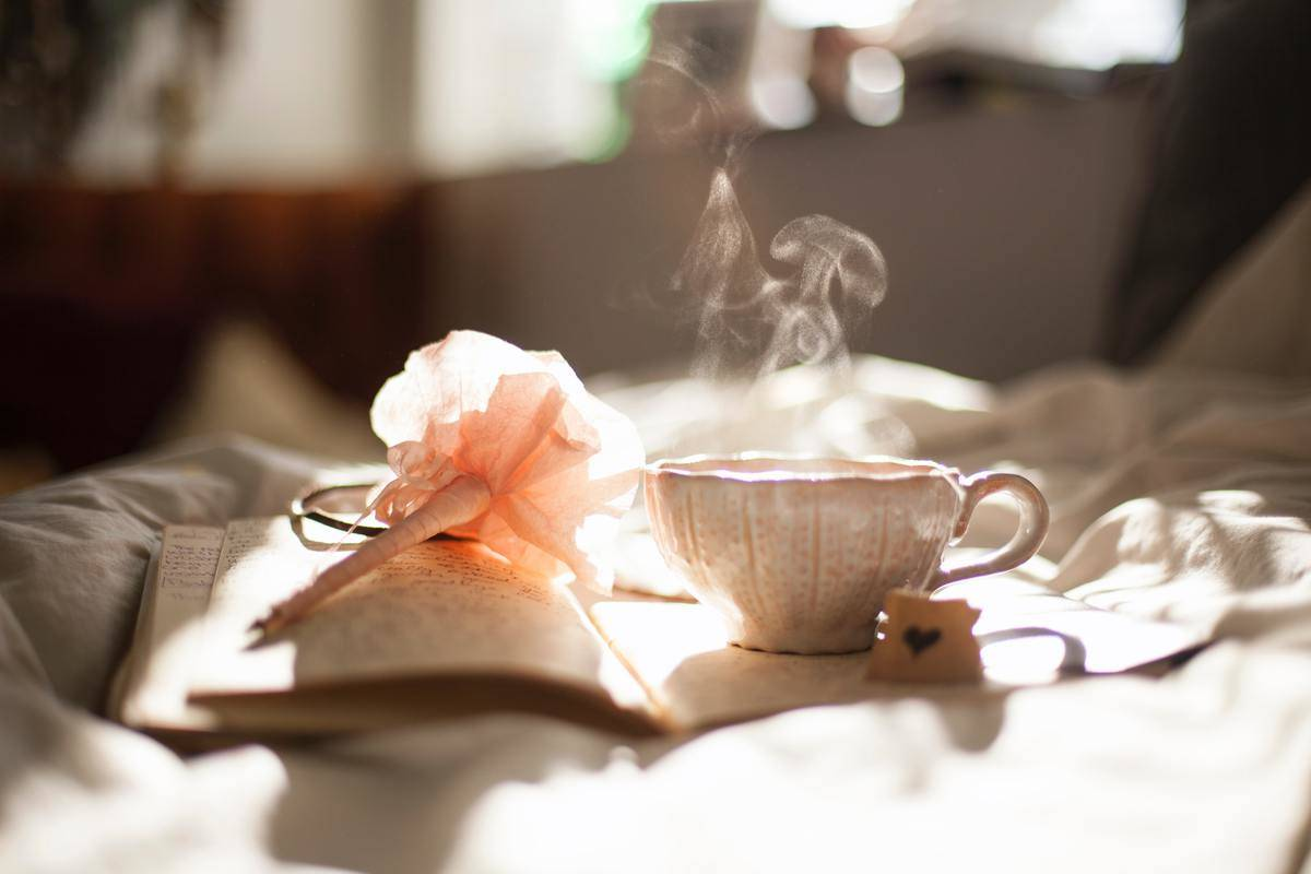 a journal and some tea on a bed