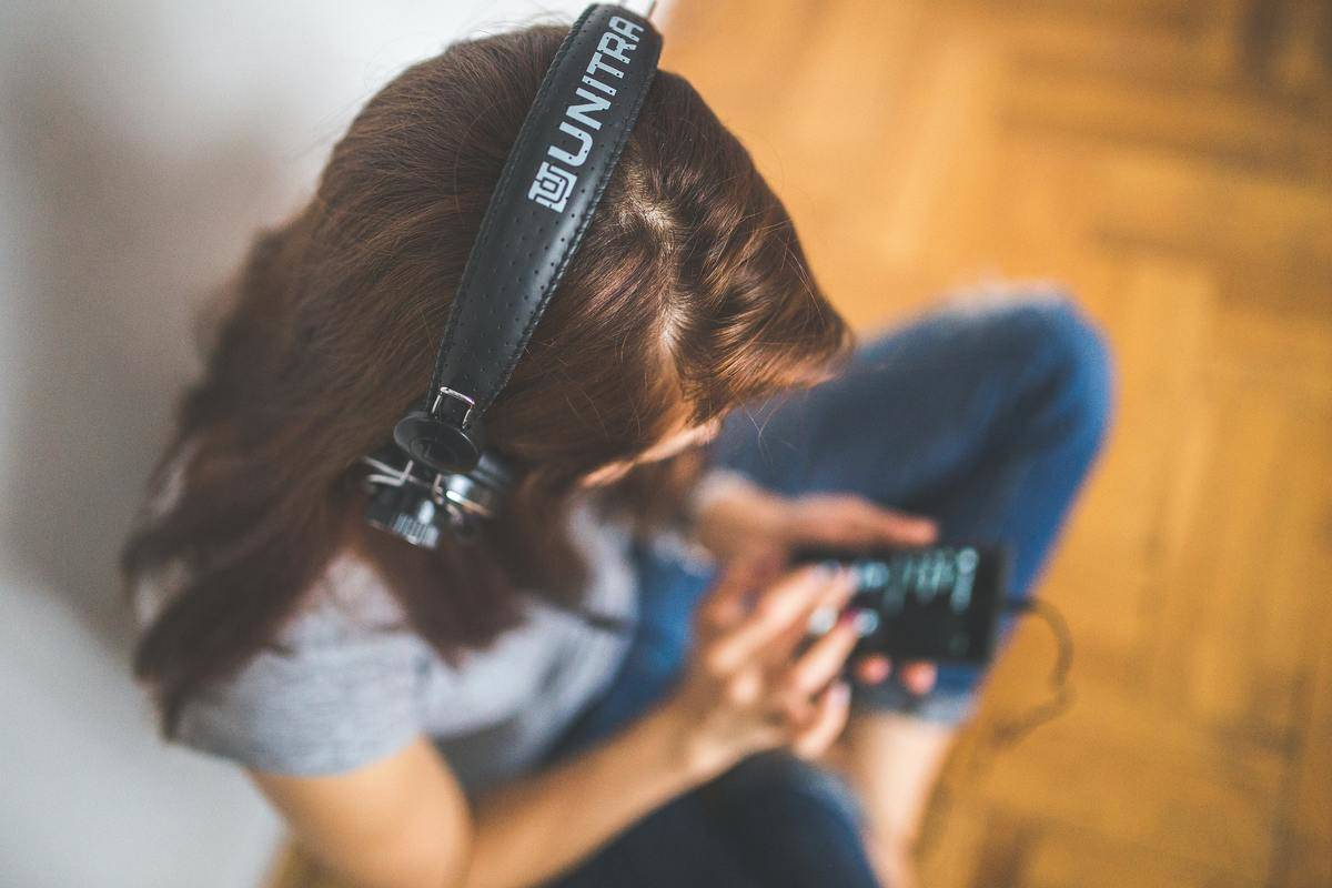 woman with headphones on seated listening to music