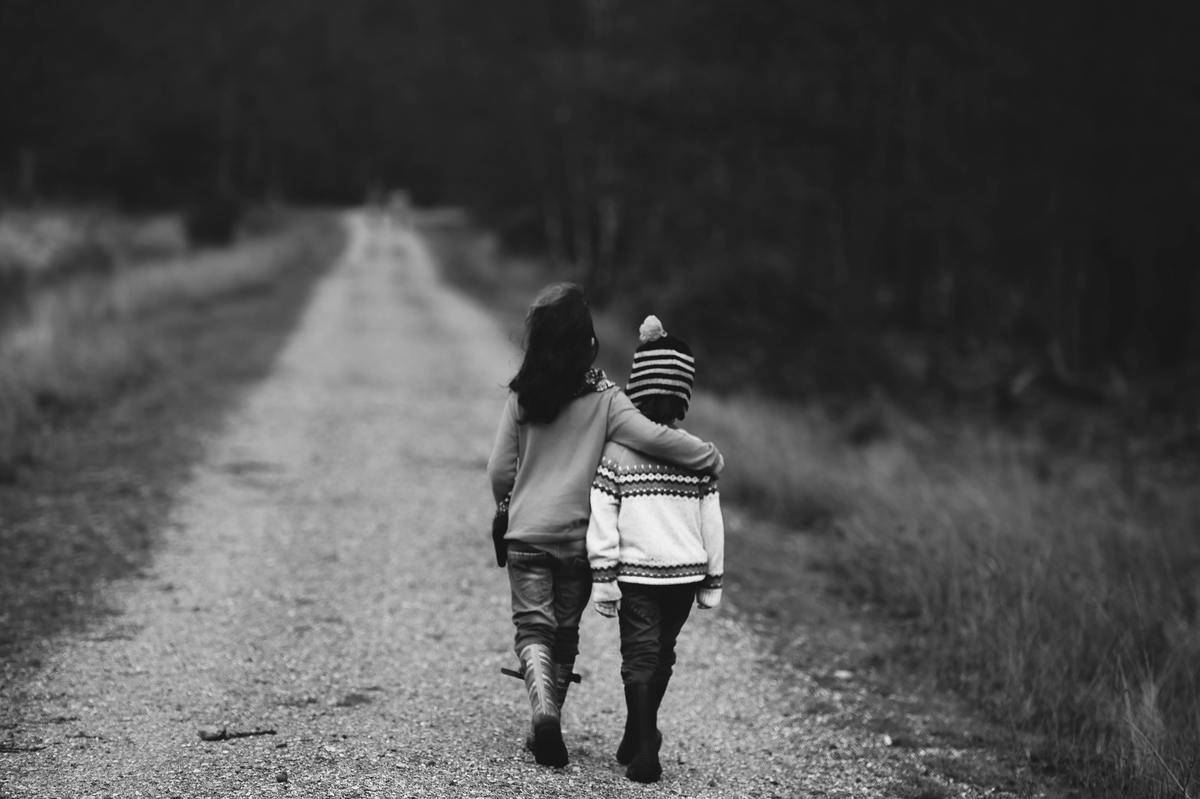 little boy and girl walking on road black and white