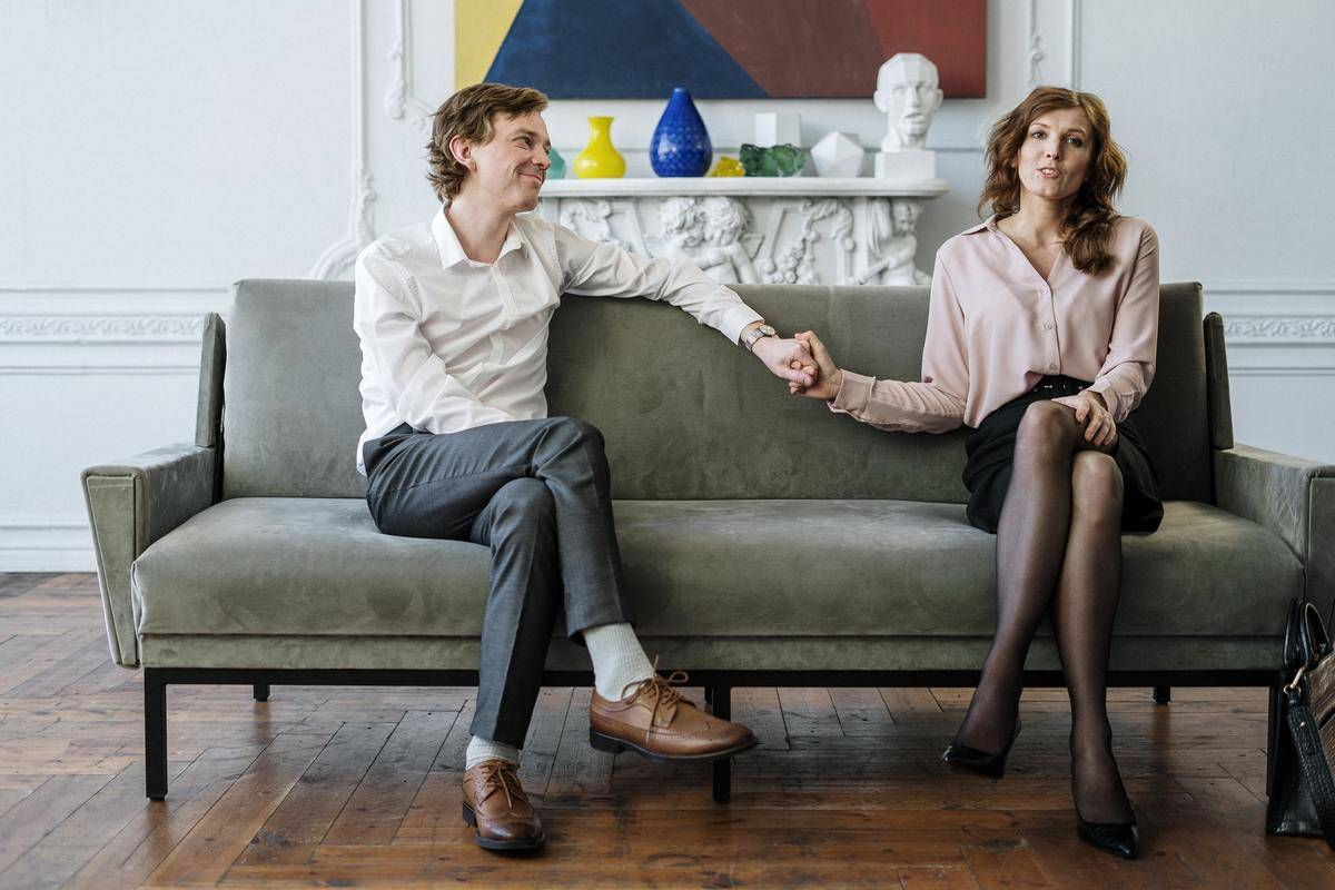 man and woman hold hands on the couch