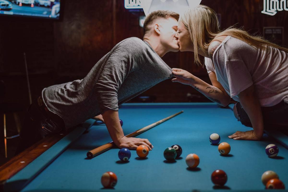 man and woman kiss over the pool table