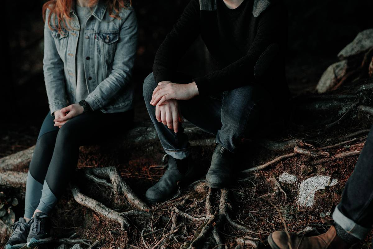 man and woman seated on log no faces not touching