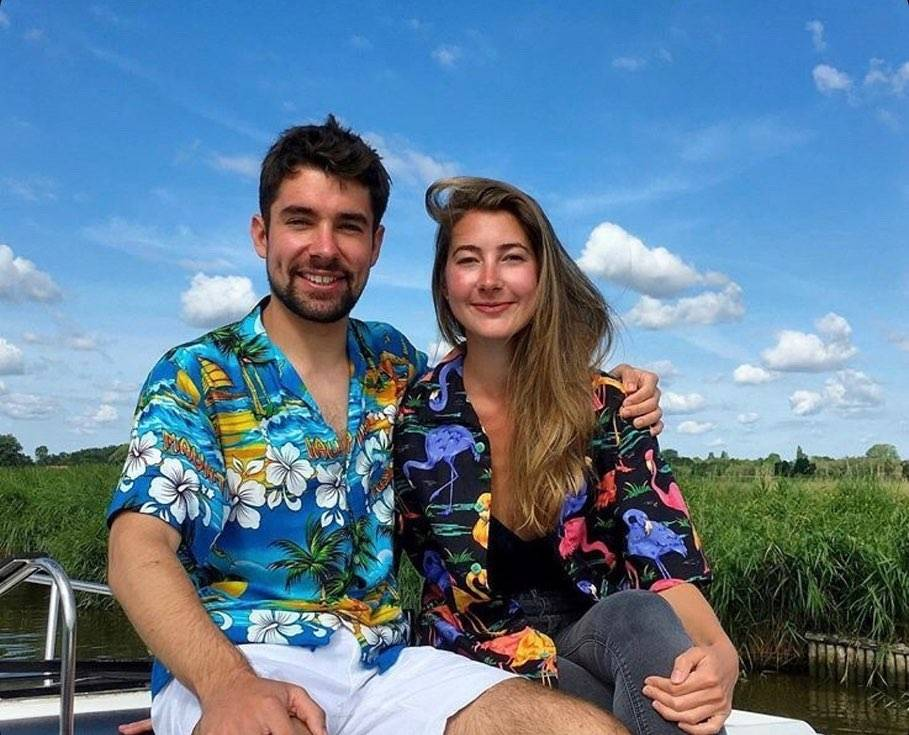 man and woman smile dressed in hawaiian shirts