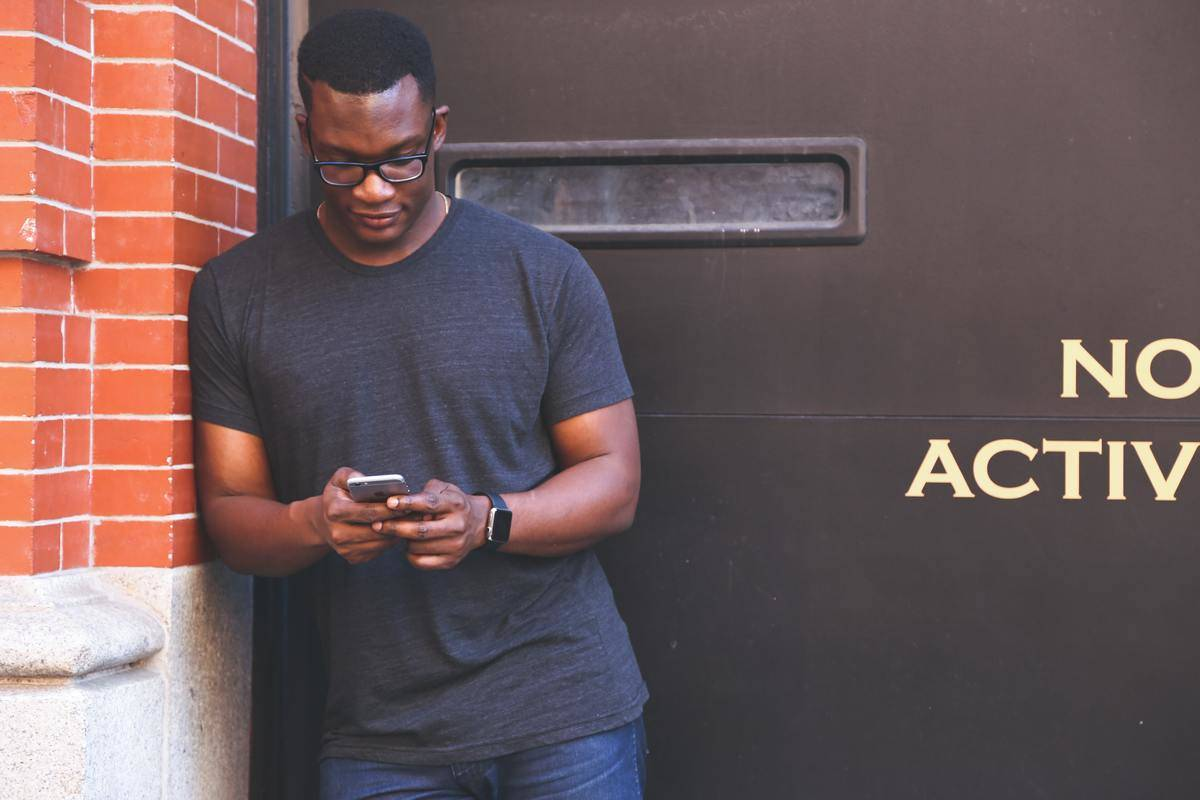 man leaning against doorway outside on phone