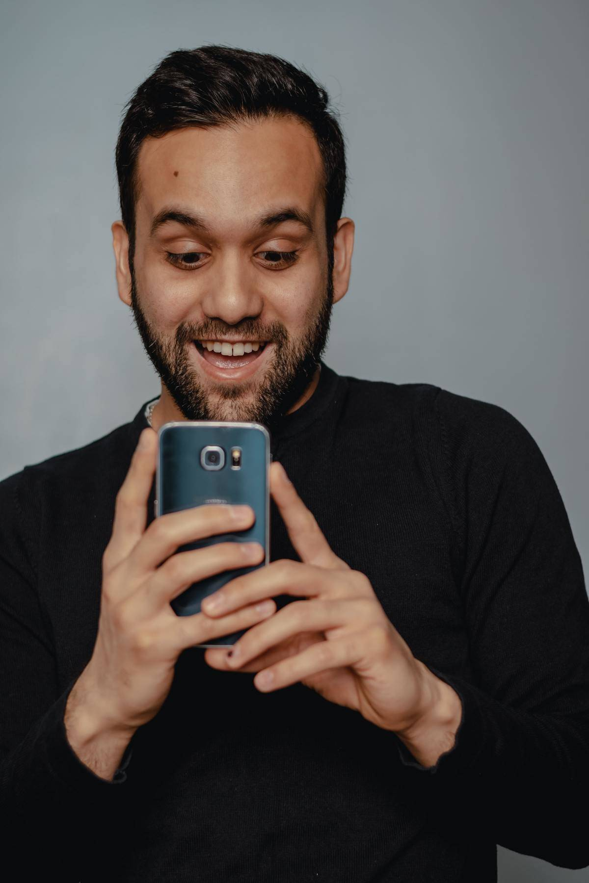 man holding phone looking at screen with surprised face