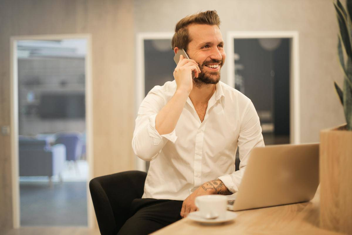 young man sitting in office at desk smiling on phone