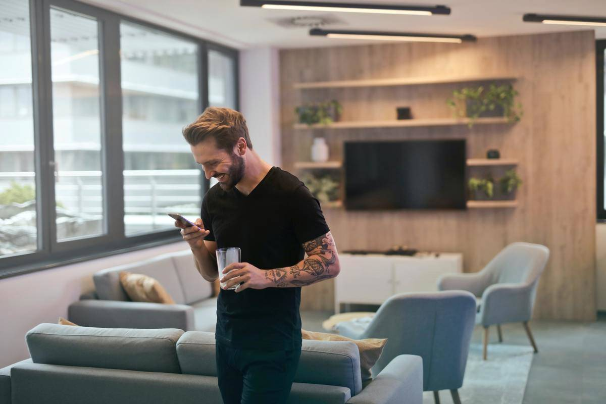 man standing in office smiling down at phone