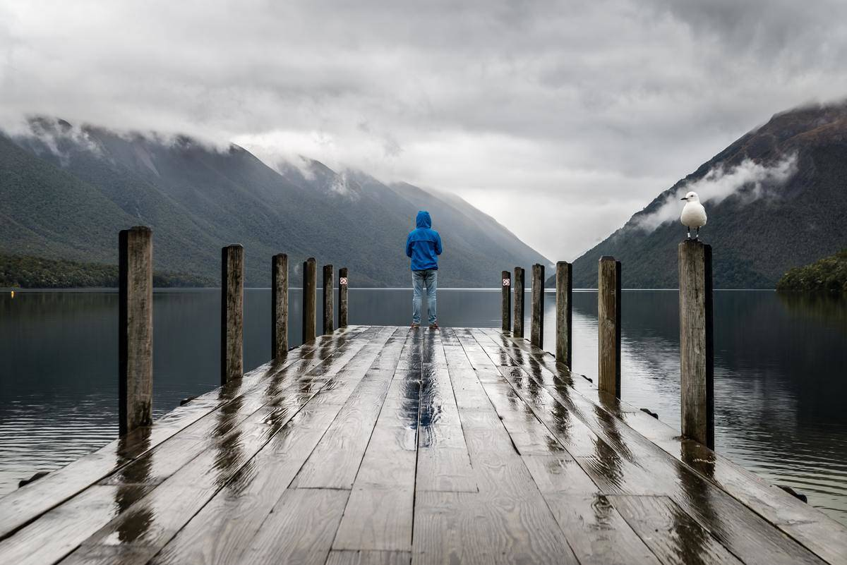 man with back to camera on dock staring out into water on gray day