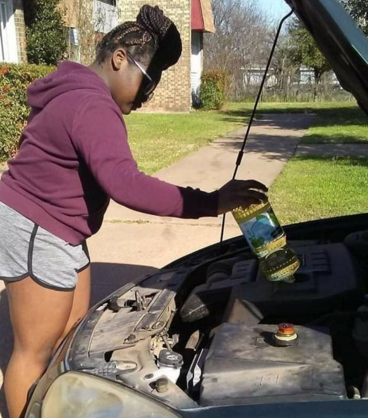 woman replacing the oil in her car with vegetable oil