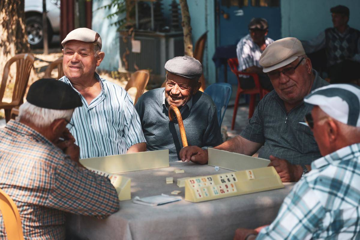 older men seated at tables outdoors playing mahjong