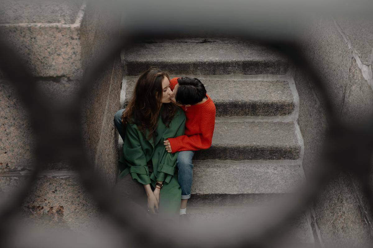couple on stairs looking through fence
