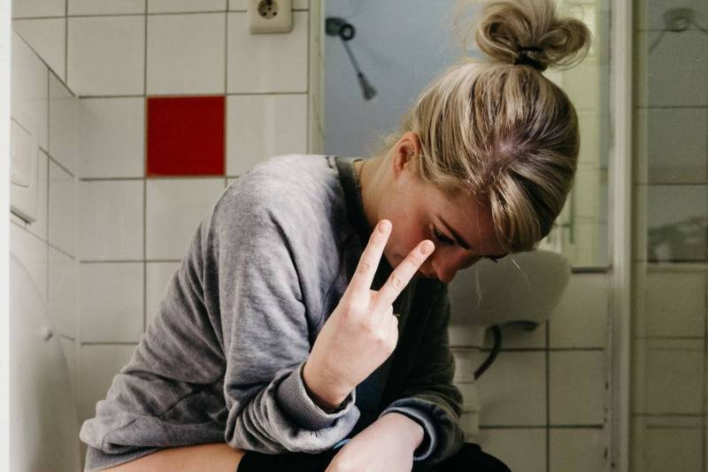 Woman sitting on toilet giving peace sign