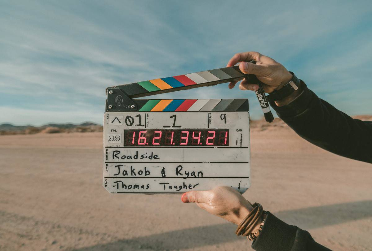 person closing clapperboard to say