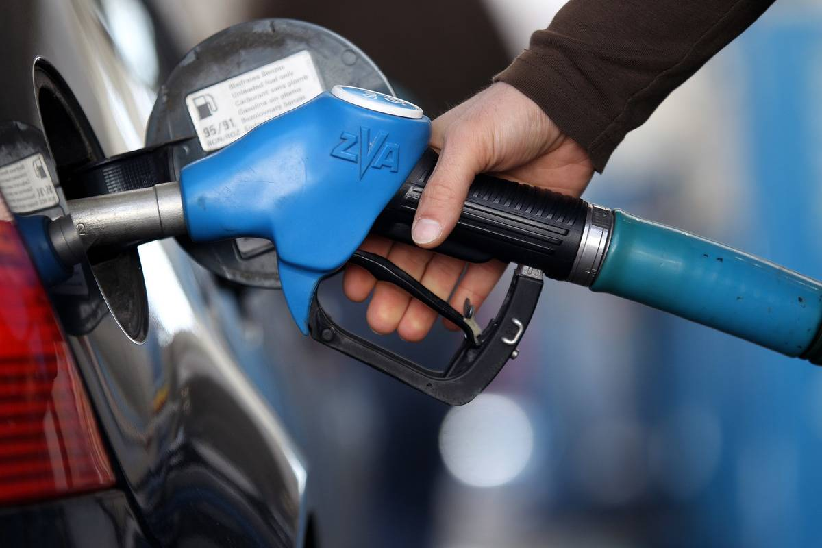 person holding nozzle refueling their car