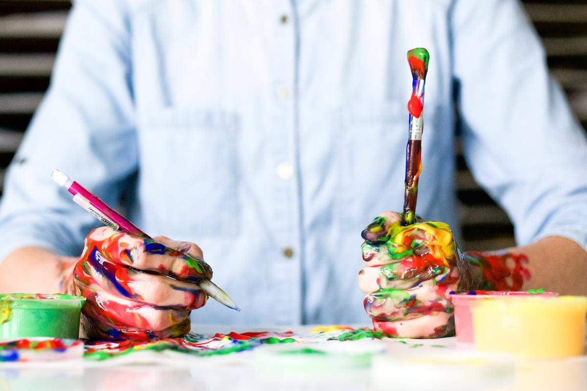 person in button shirt holds paint brush with lots of paint