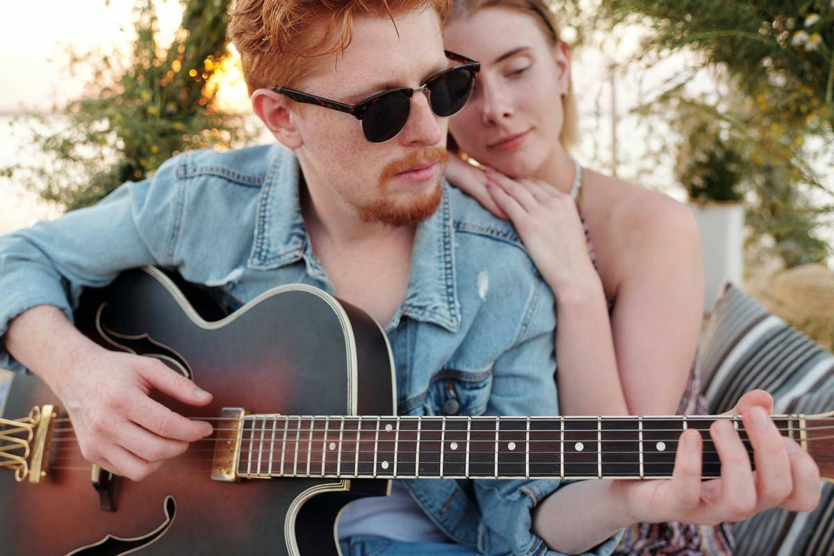 man playing guitar, woman hugging him from behind