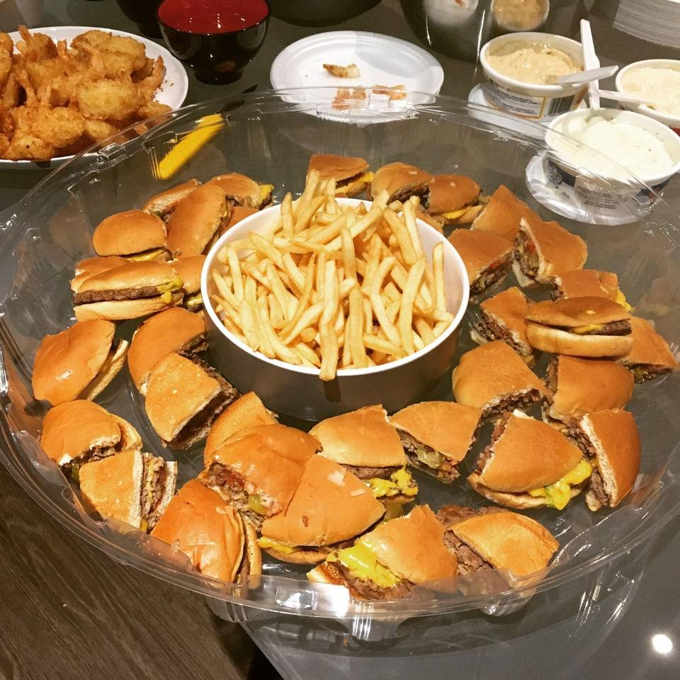 someone's boyfriend brought a bunch of cut up fast food cheese burgers and fries for a potluck