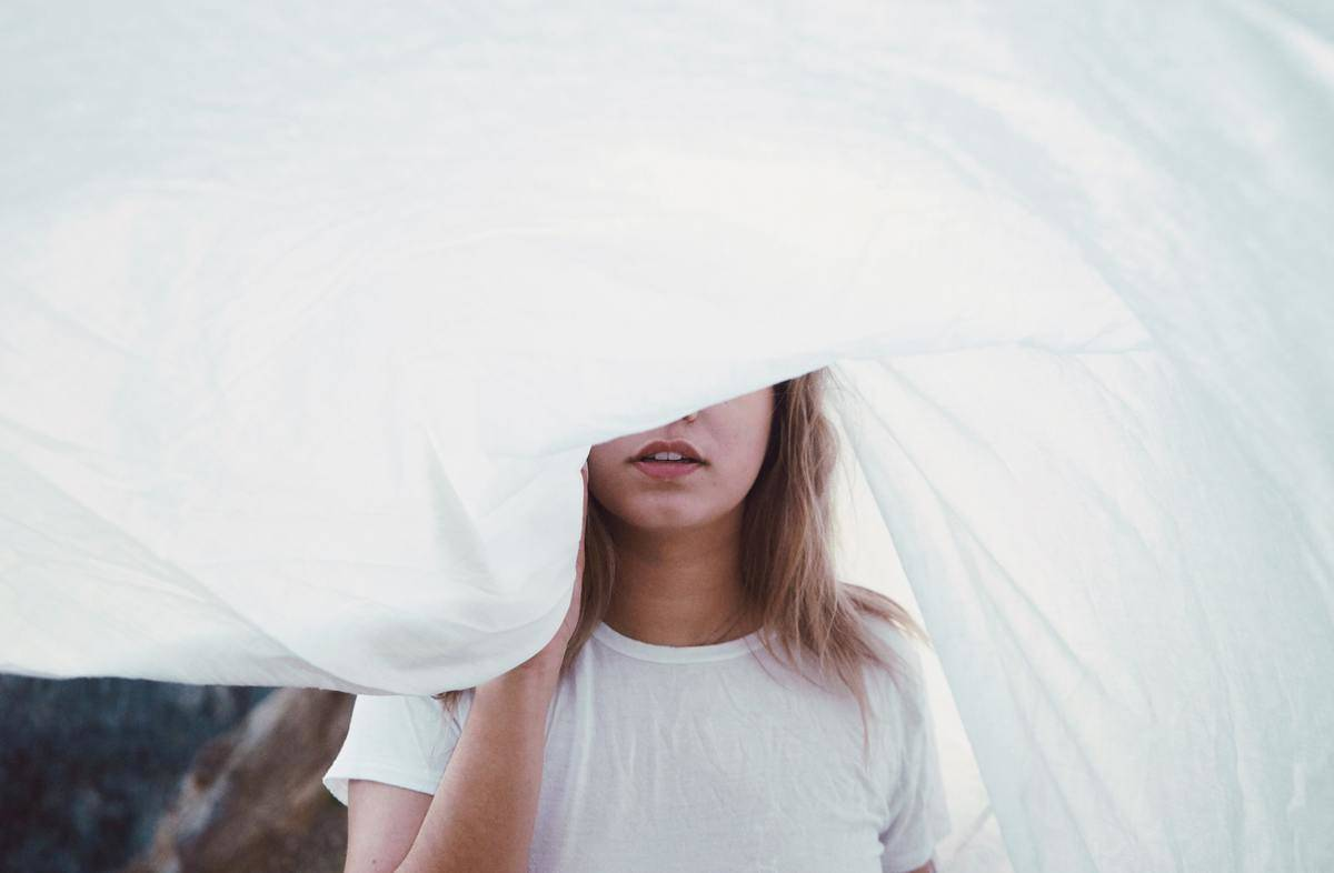 woman with a sheet over her face