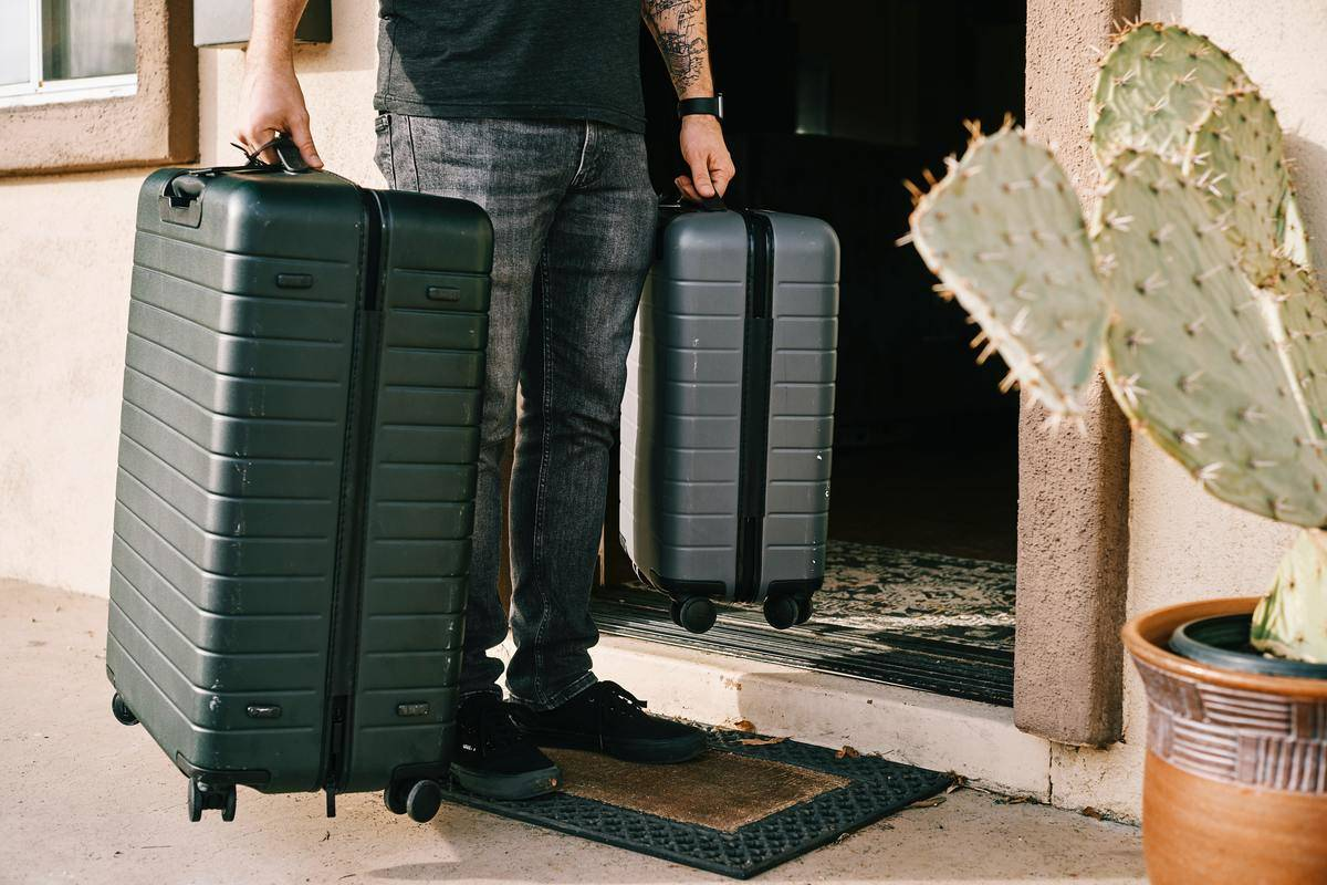 man carries luggage out of the house