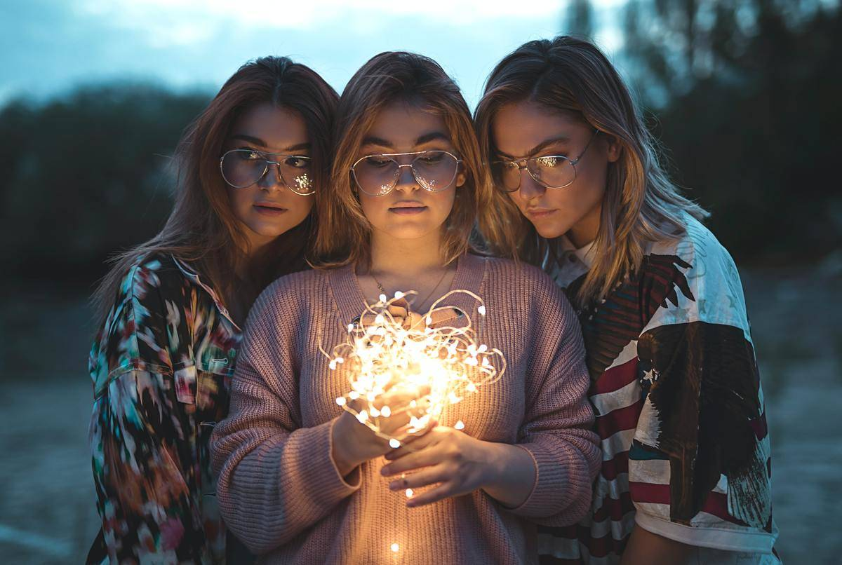 three women looking into ball of string lights