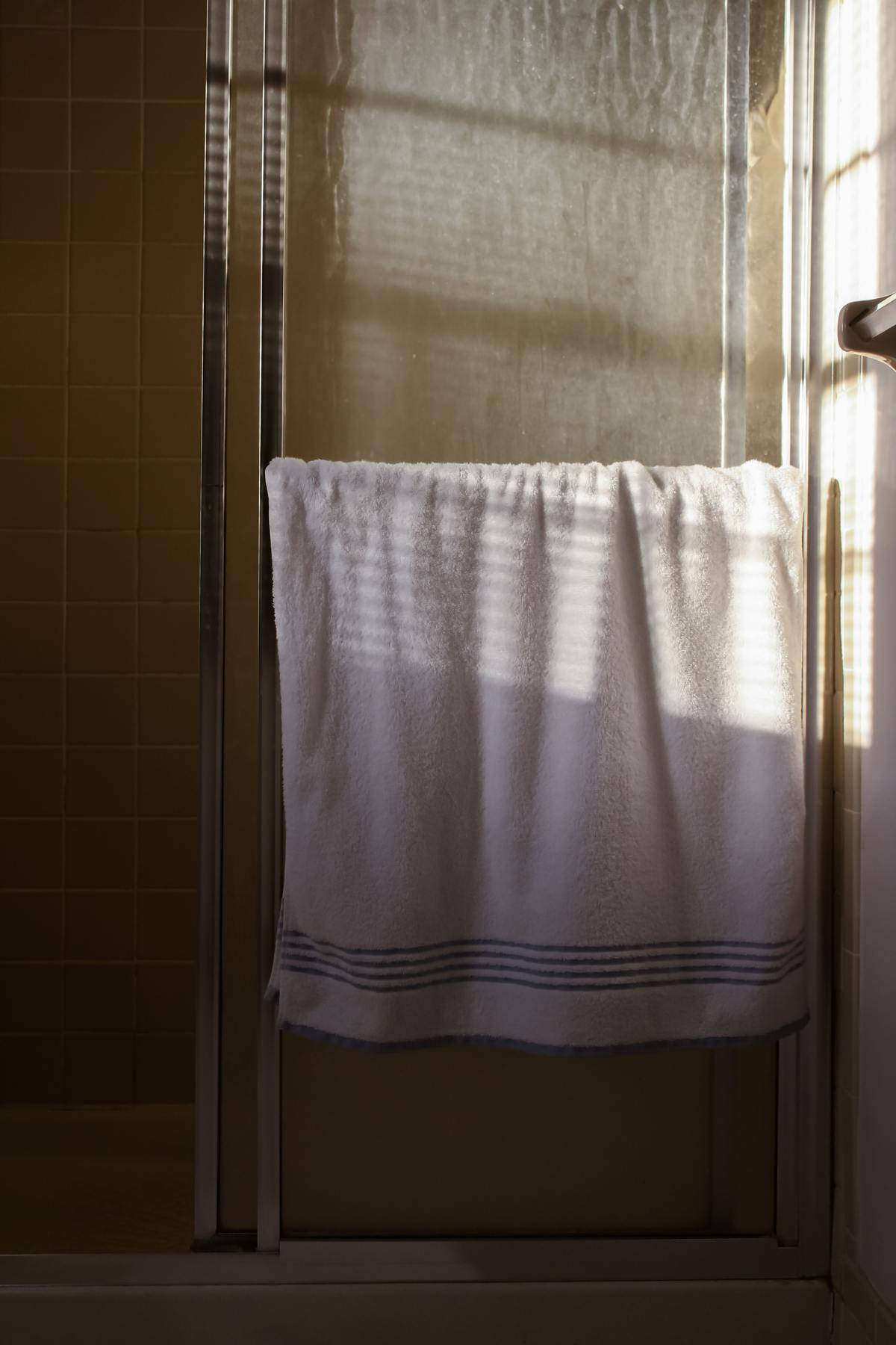 towel hanging on handle of shower