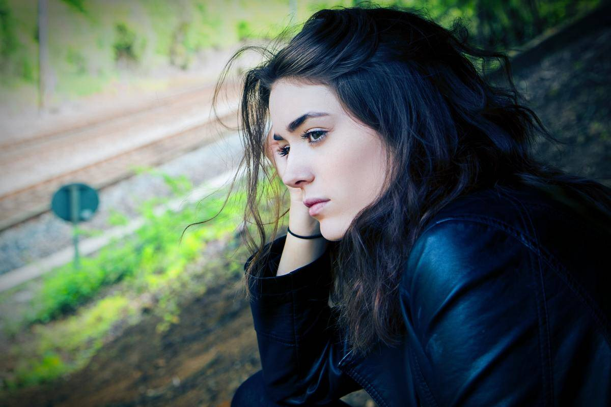 woman sitting by train tracks