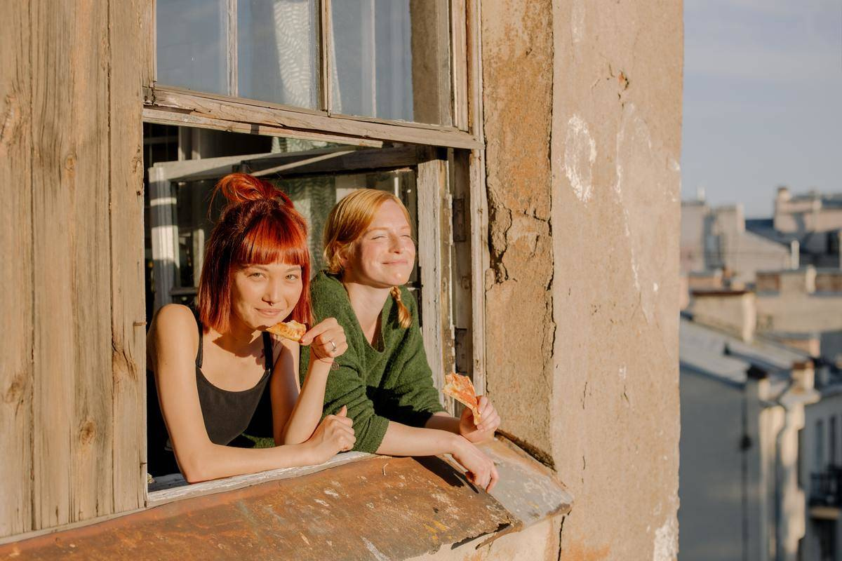 two women leaning out window smiling into sunshine