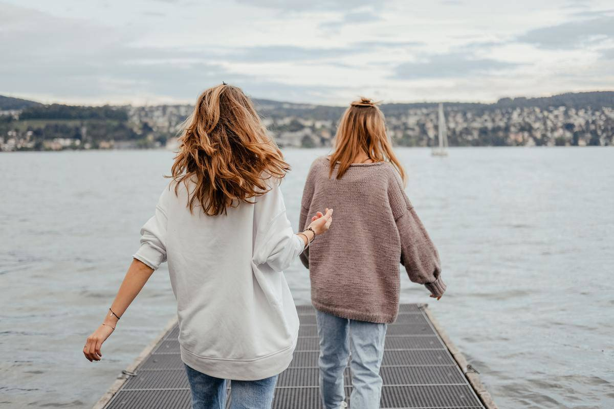 two girls standing on dock looking away from camera, one ahead of the other