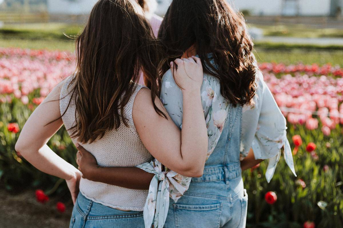 women embracing backs facing camera in flower field
