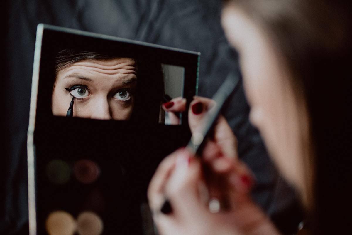 woman applies mascara in tiny mirror