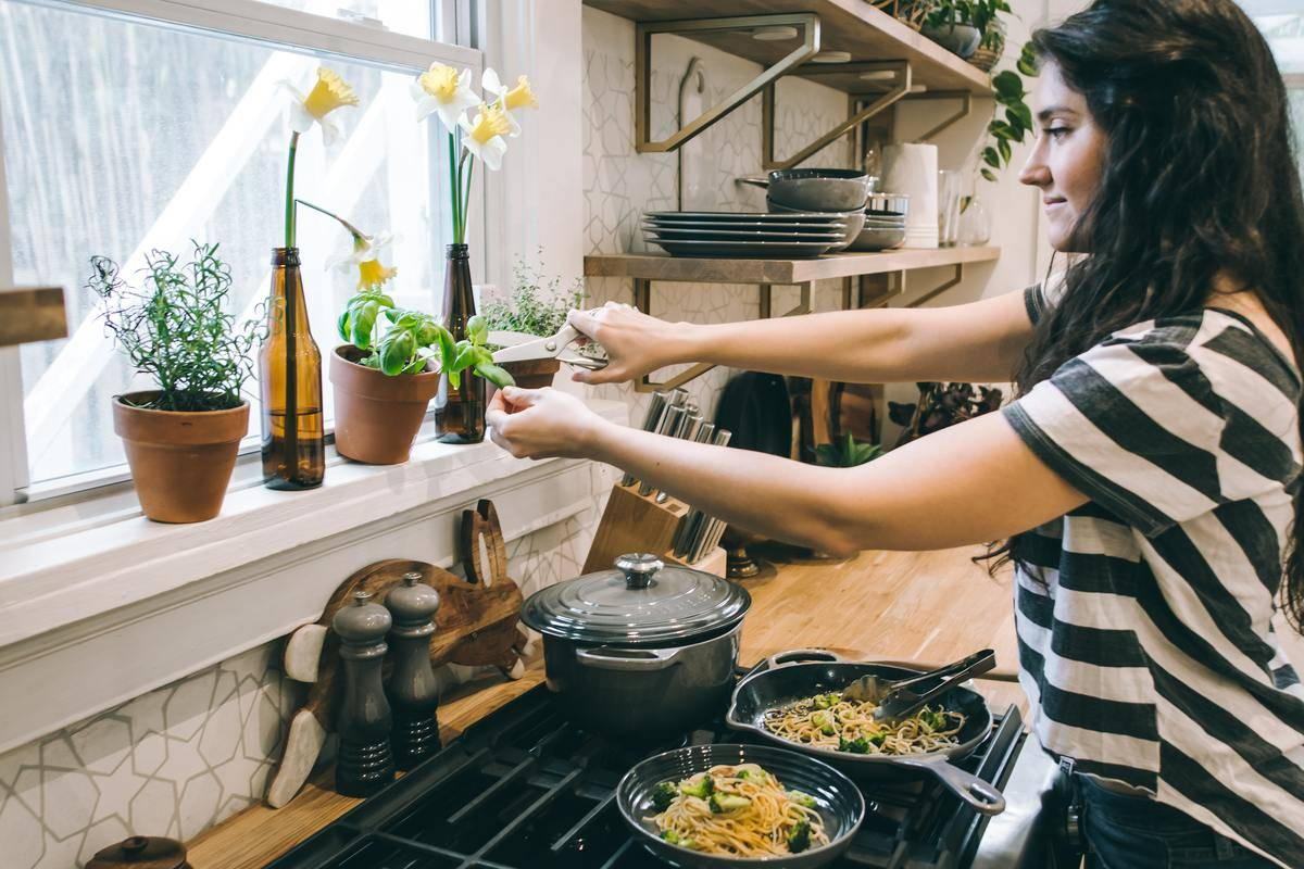 woman cooking in kitchen standing at stove