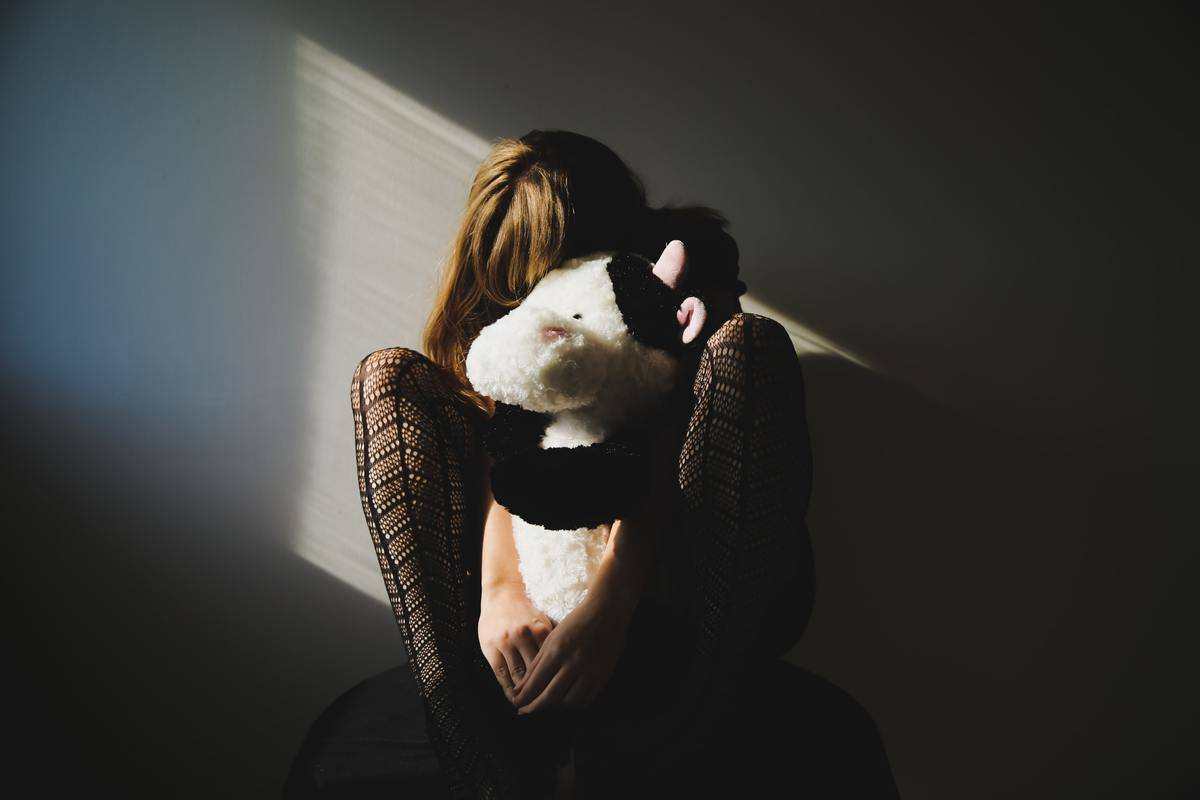 woman in stockings hides her face into stuffed animal