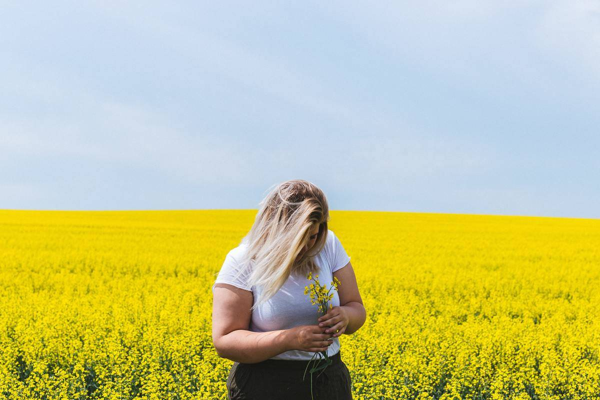 woman holding flower looking sad head down in flower field
