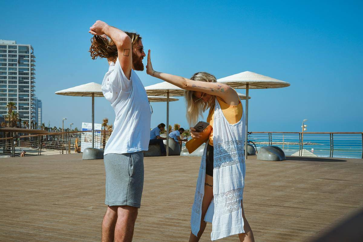 man with arms raised above head woman reaching out with one hand